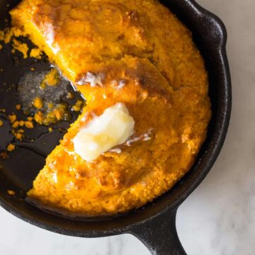 Pumpkin cornbread in a cast iron skillet with a piece cut out and butter on top.