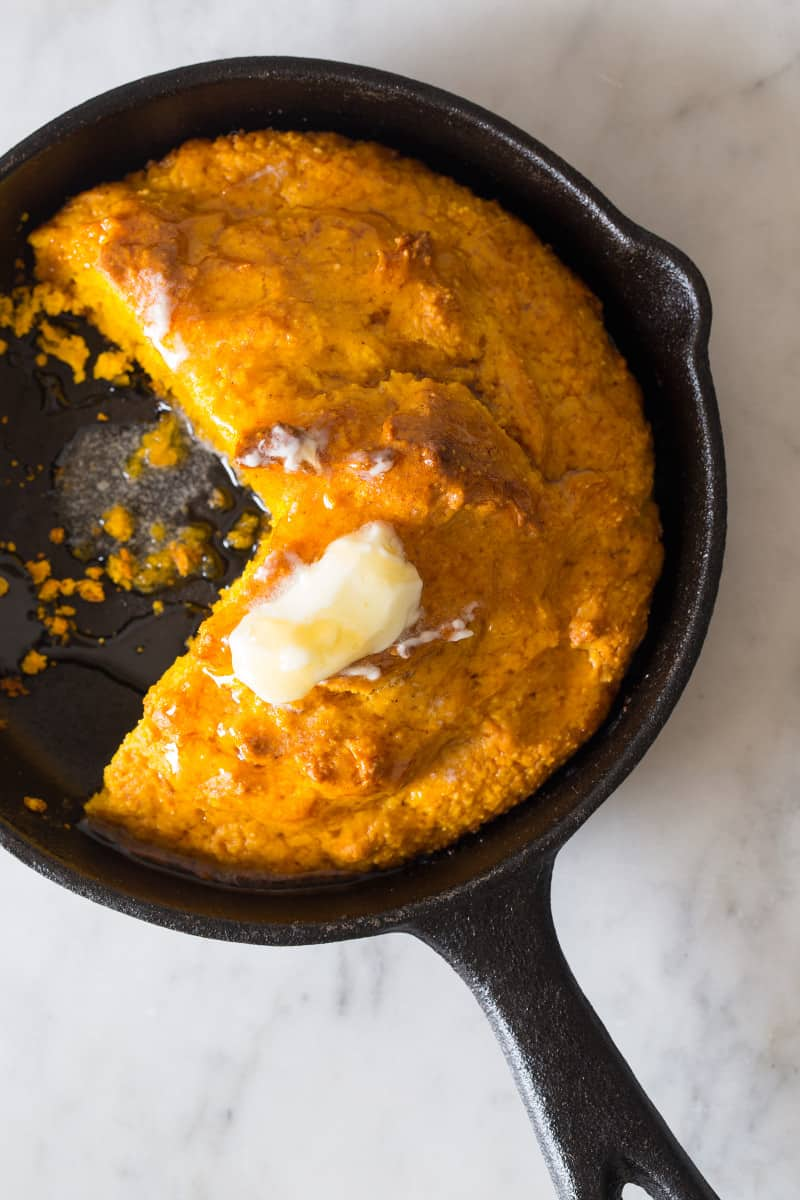 A close up of pumpkin cornbread with butter in a skillet and a piece cut out.