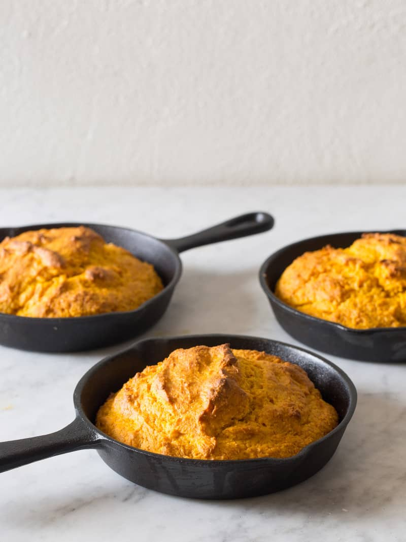 Three cast iron skillets with pumpkin cornbread.