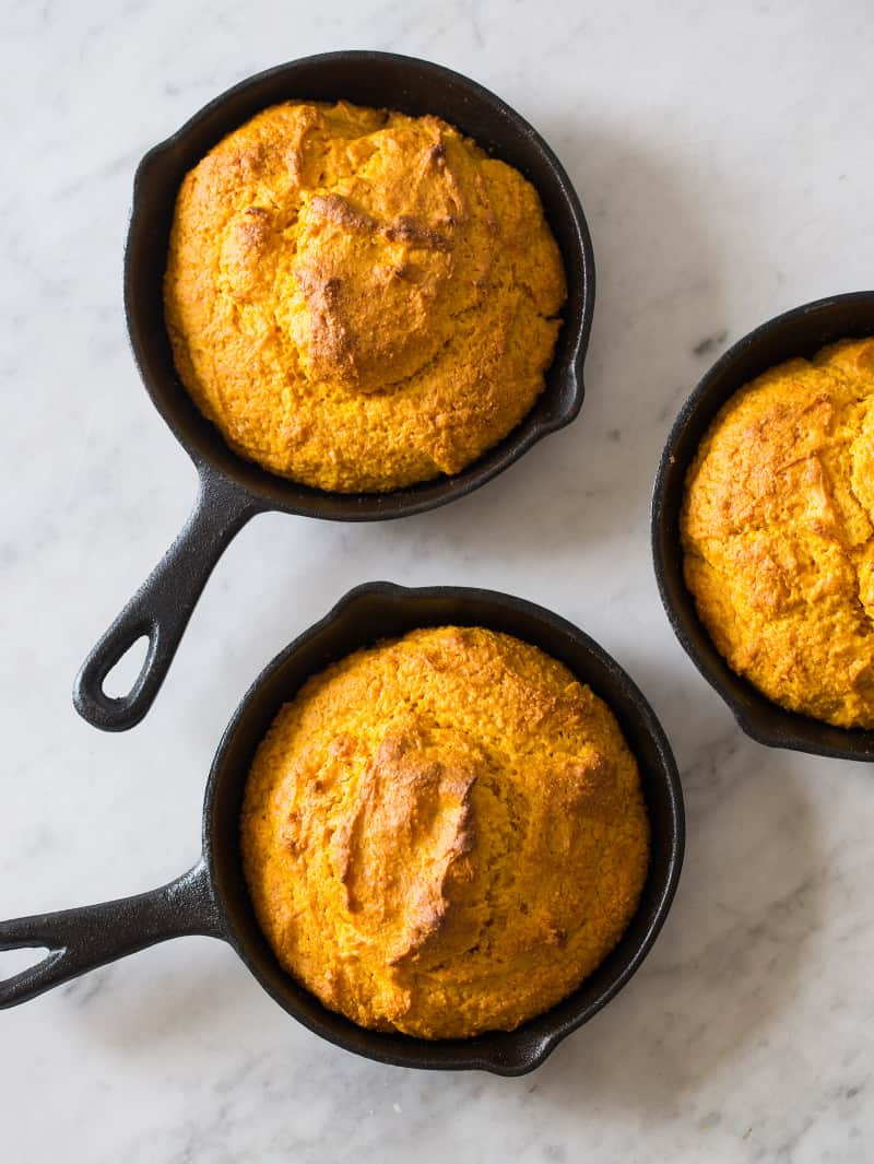 Three small skillets of pumpkin cornbread freshly baked.