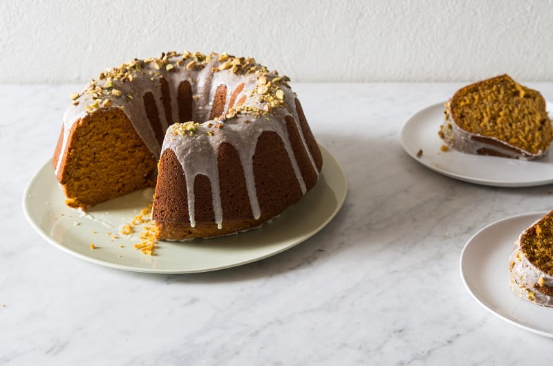 Pumpkin bundt cake with two slices taken out sitting on two plates next to it.