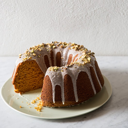 A whole pumpkin bunt cake with pistachio glaze with a slice taken out.