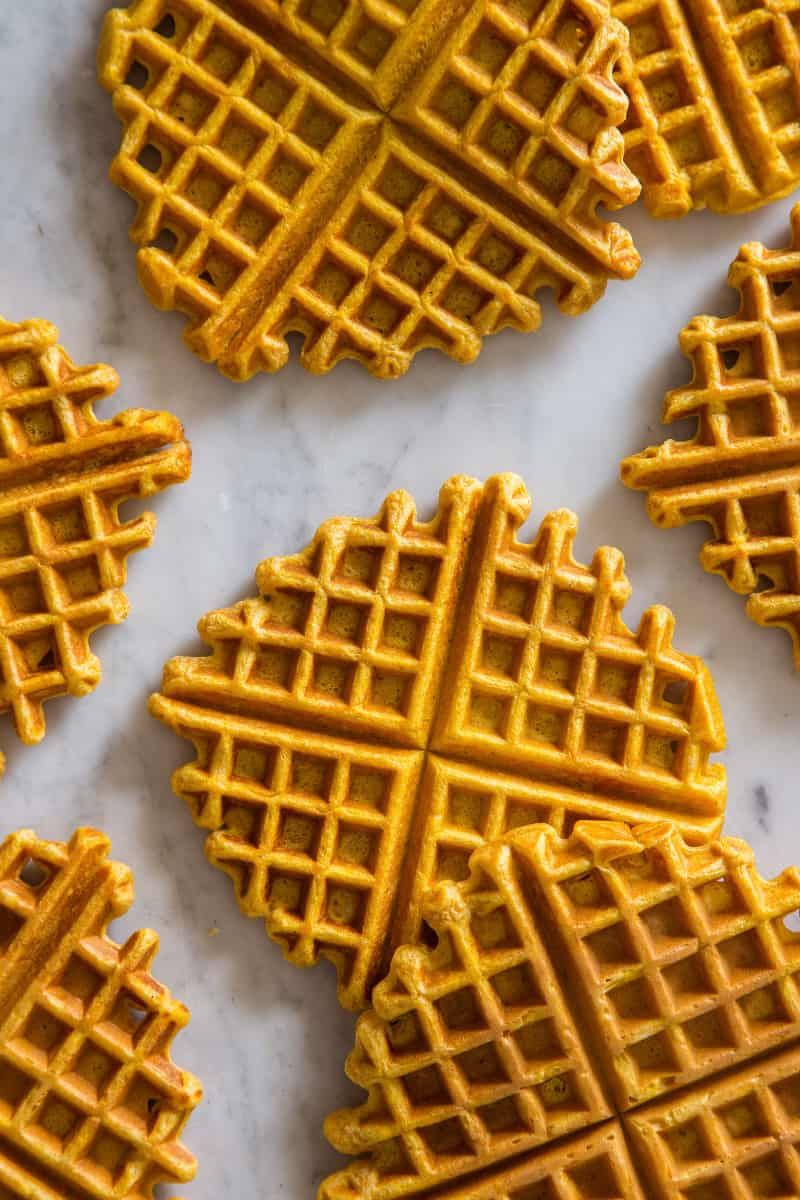 Pumpkin spiced waffles laid out on a marble kitchen counter.