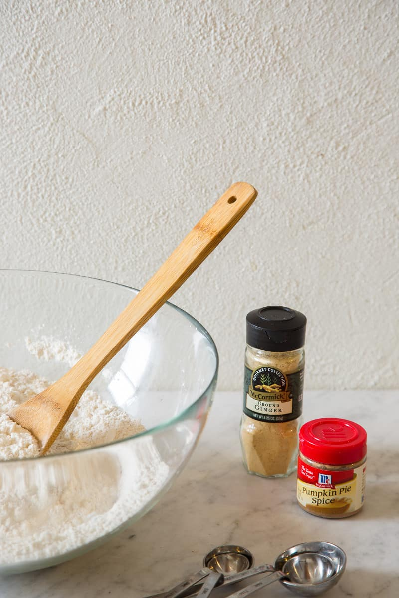 A large bowl of dry ingredients with a wooden spoon next to a few spice bottles.
