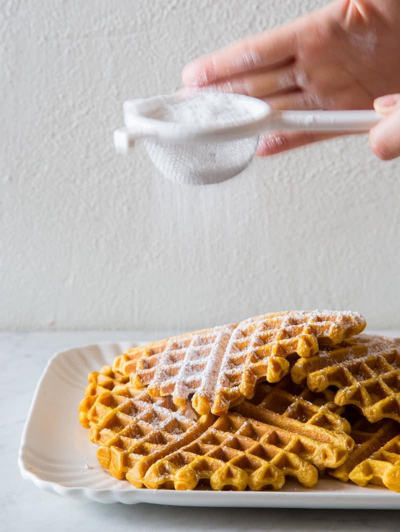 Stacked pumpkin spiced waffles with powdered sugar being sifted on top.
