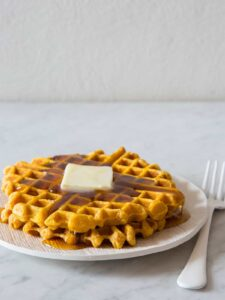 Stacked pumpkin spiced waffles with butter and syrup on a plate with a fork.