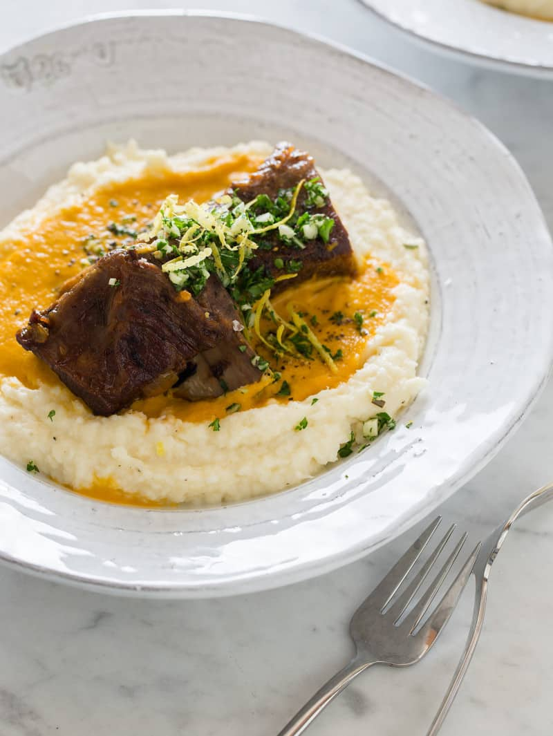 A close up of braised short ribs over polenta with forks.