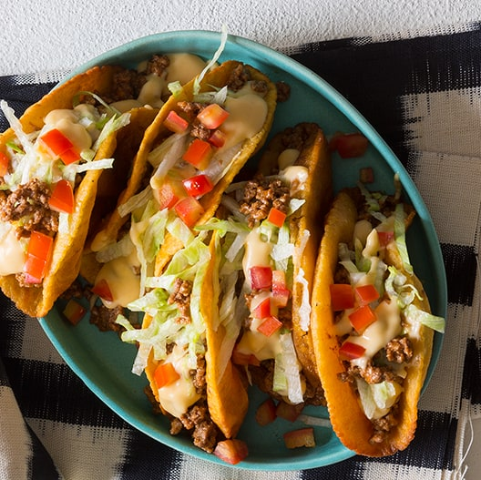 A plate of crunchy beef tacos with a cheese sauce on top.