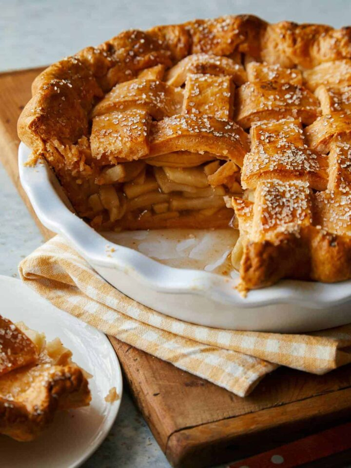 A close up of a whole brown butter apple pie with slice removed.