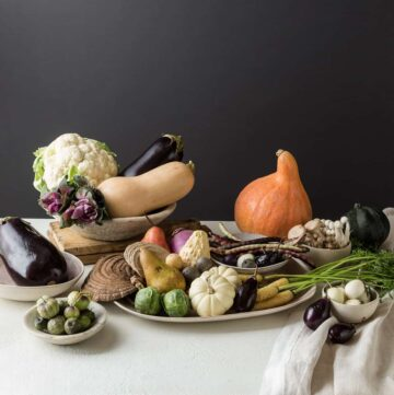 A flowerless Thanksgiving centerpiece made with a variety of fruits and vegetables.