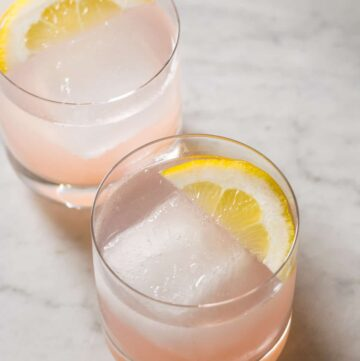 A close up of red grapefruit and rum spritzers garnished with lemon slices.