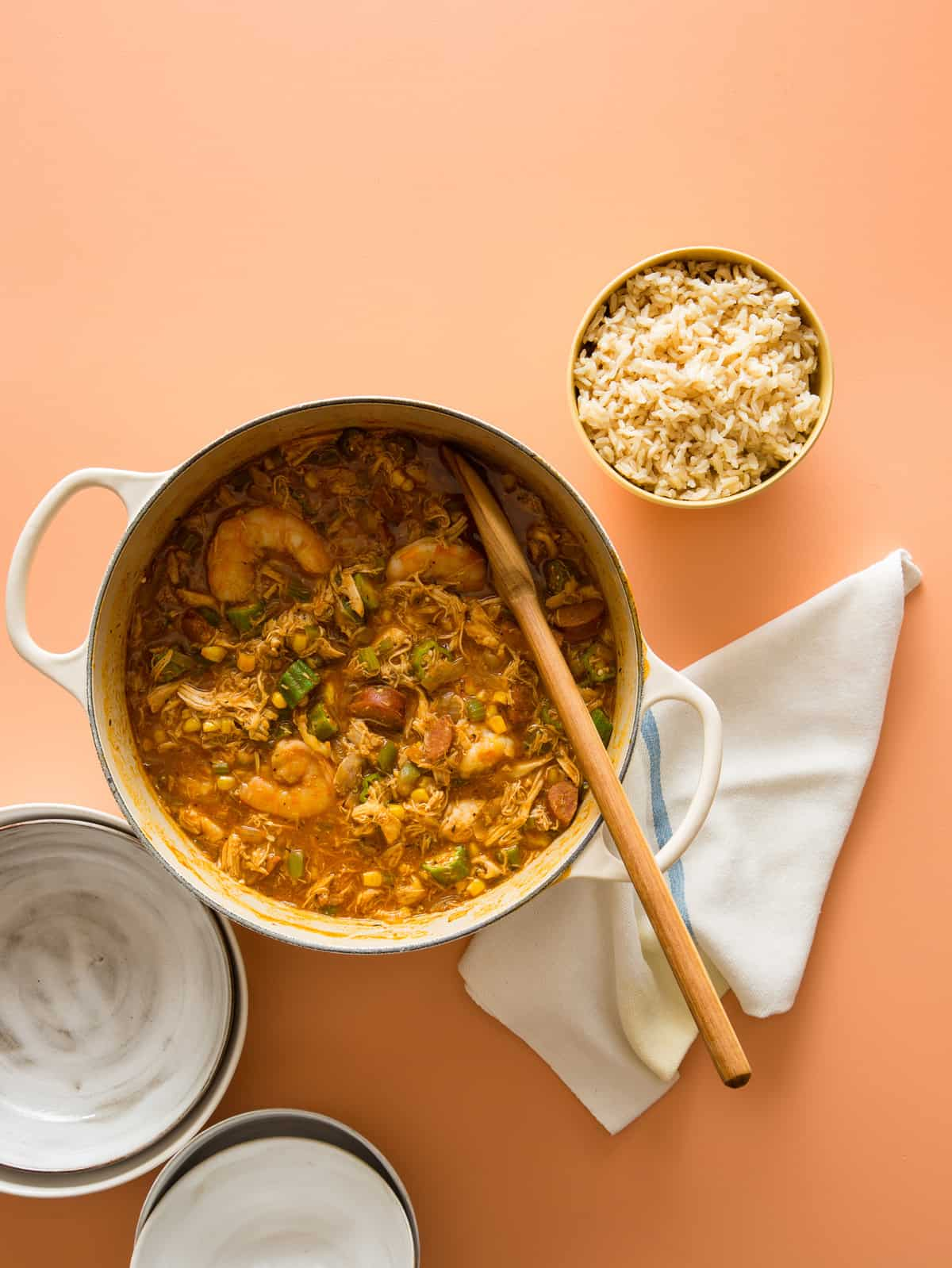 A pot of chicken and andouille gumbo with a bowl of rice and a wooden spoon.