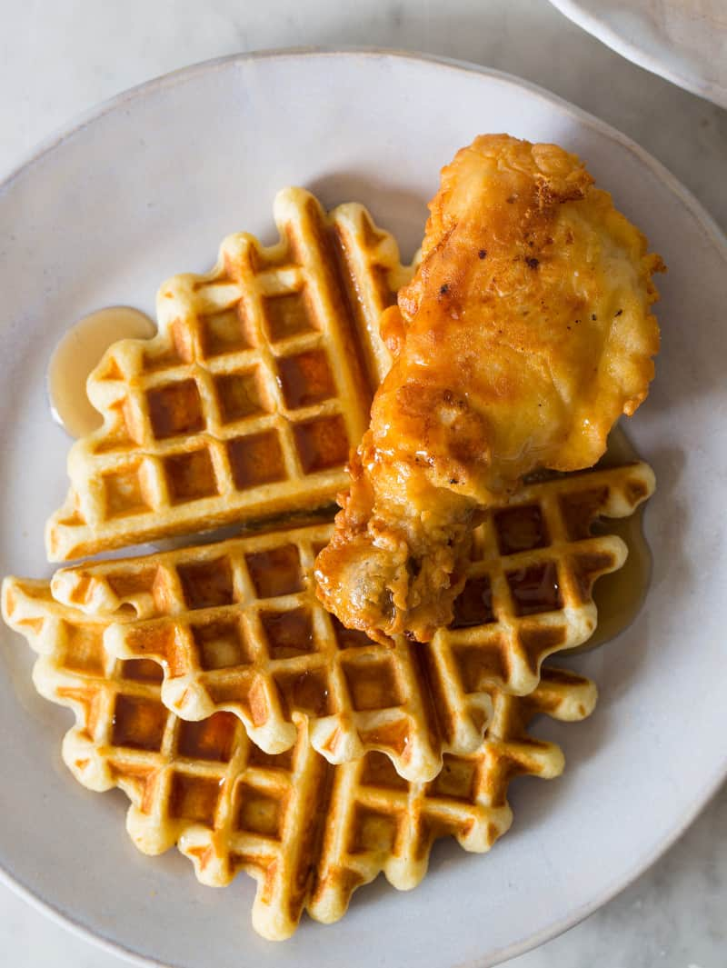 Fried chicken and waffles with syrup on a plate.