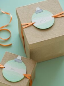 Dip dye ornament gift tags tied onto brown gift boxes.