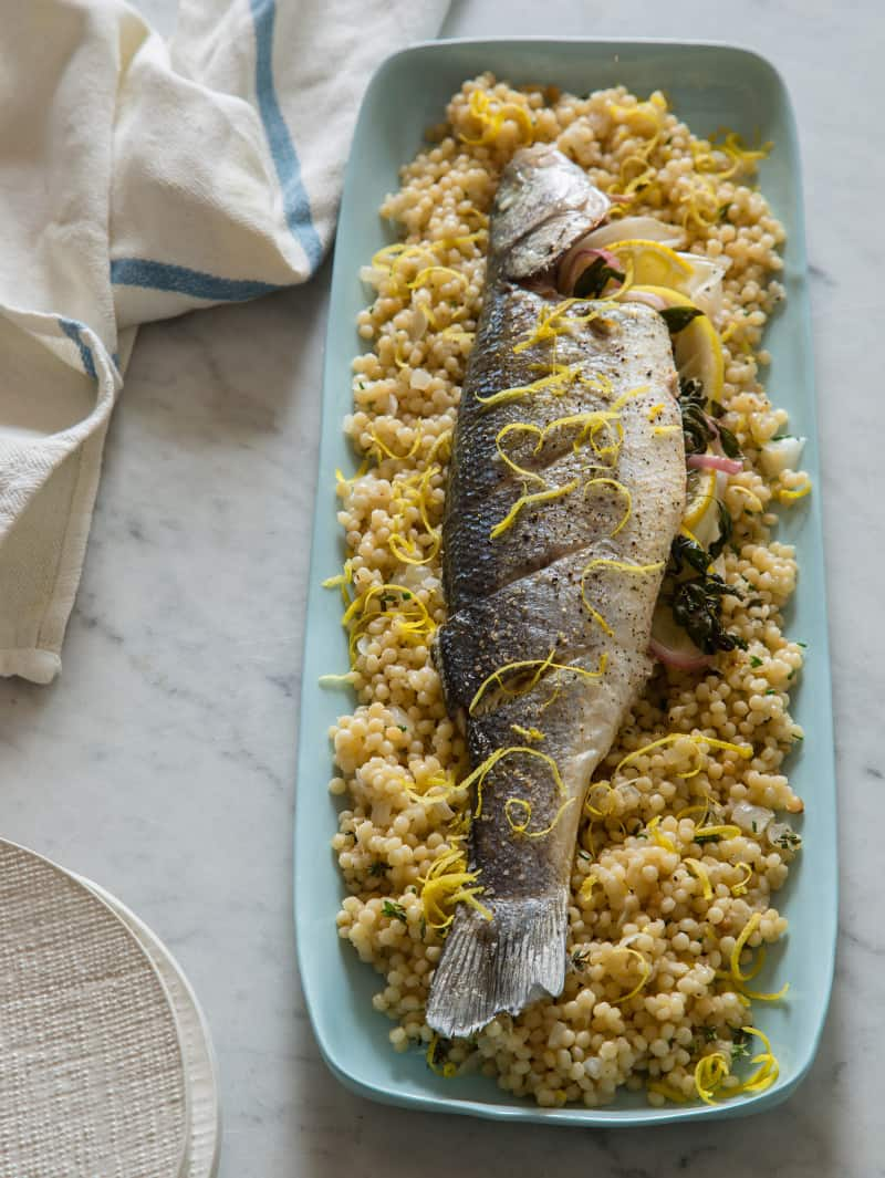 A platter of oven roasted branzino on a bed of cous cous.