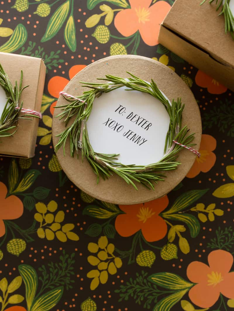 A close up of a rosemary wreath gift toppers tied to a round brown gift box.