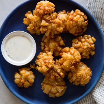 Baby bloomin' onions on a dark blue plate with a side of buttermilk ranch dipping sauce.