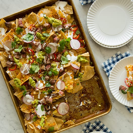 A baking sheet of Carne Asada Nachos with plates on the side and napkins.