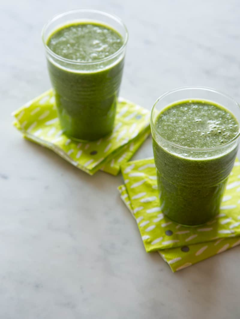 Two cups of coconut kale and banan smoothies on a kitchen counter with napkins nearby.