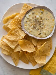 A bowl of roasted poblano queso fondido on a plate of tortilla chips.