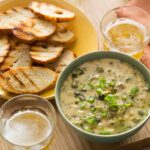 A bowl of roasted broccoli and white cheddar queso fundido with crostini and drinks.