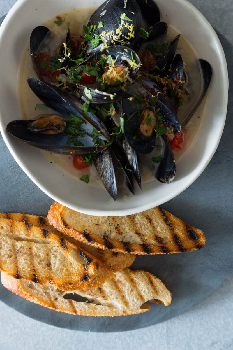 A bowl of white wine steamed mussels with a stack of grilled bread next to it.