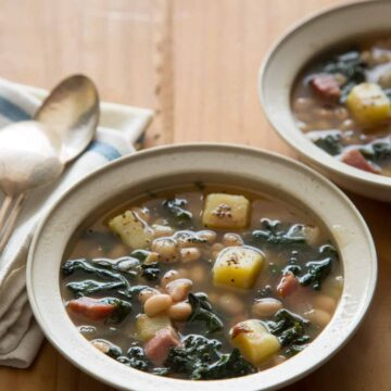 Bowls of hearty white bean and kale soup with napkins and spoons.