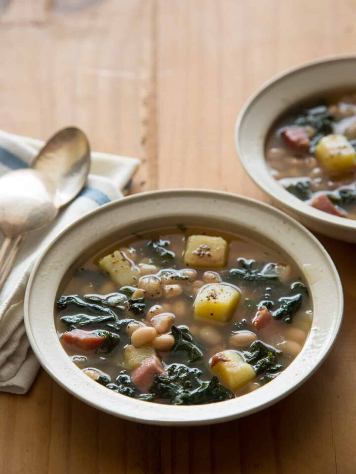 Bowls of hearty white bean and kale soup with napkins and spoons, an easy dinner recipe.
