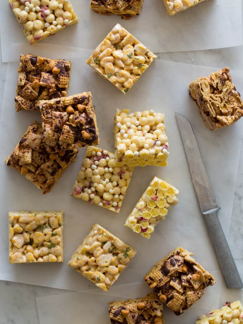 Marshamllow cereal treats on a surface with a knife and parchment.