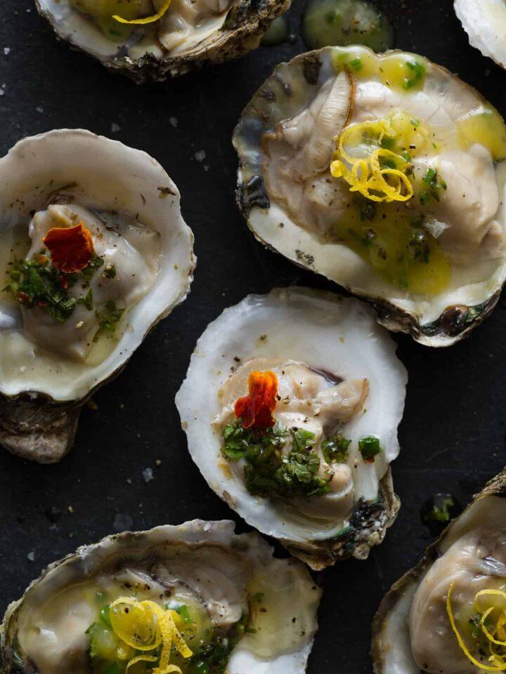 A close up of roasted oysters with a variety of garnish.