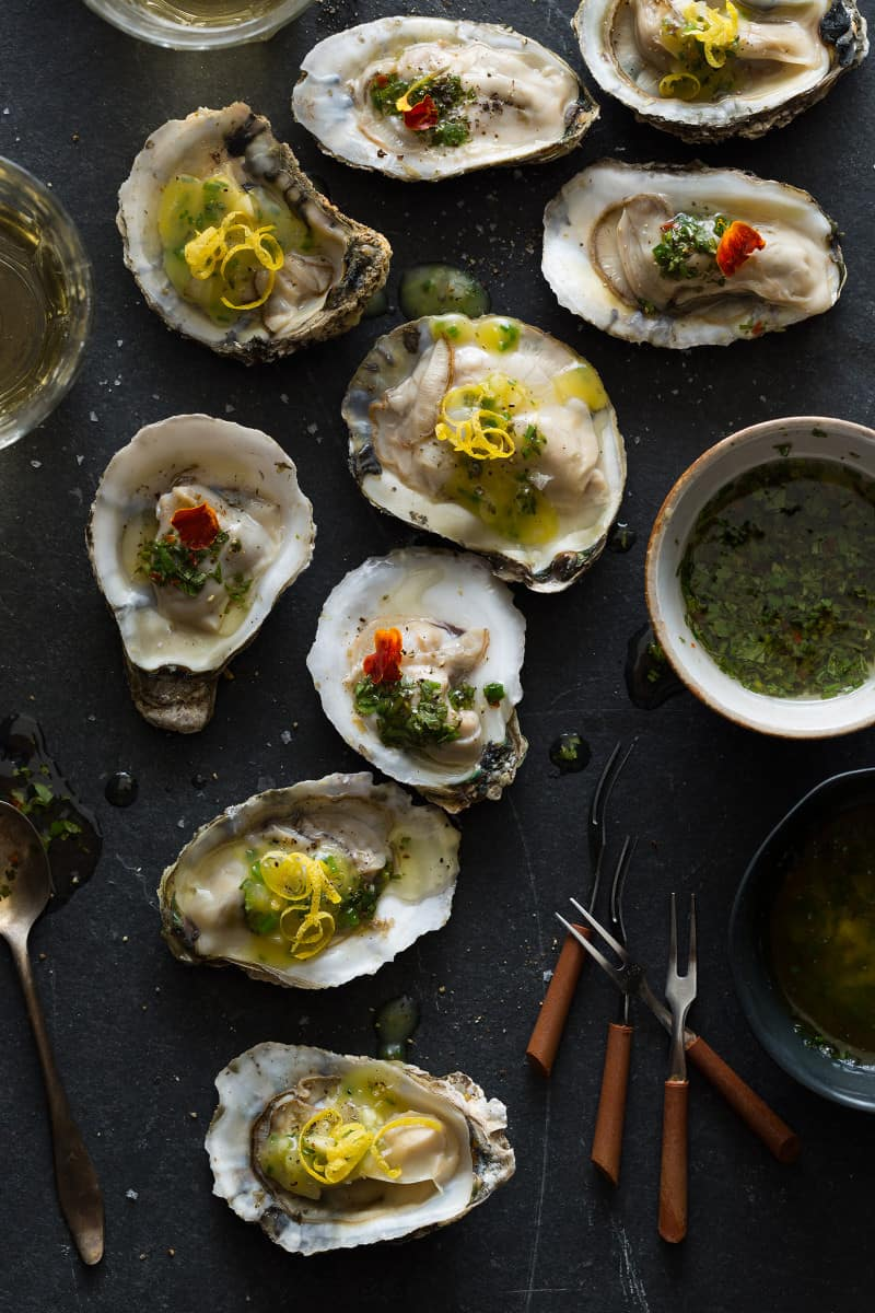 Roasted oysters on a surface with dipping sauces.