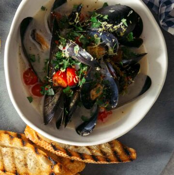 A bowl of white wine steamed mussels on a plate with bread, forks, and drinks.