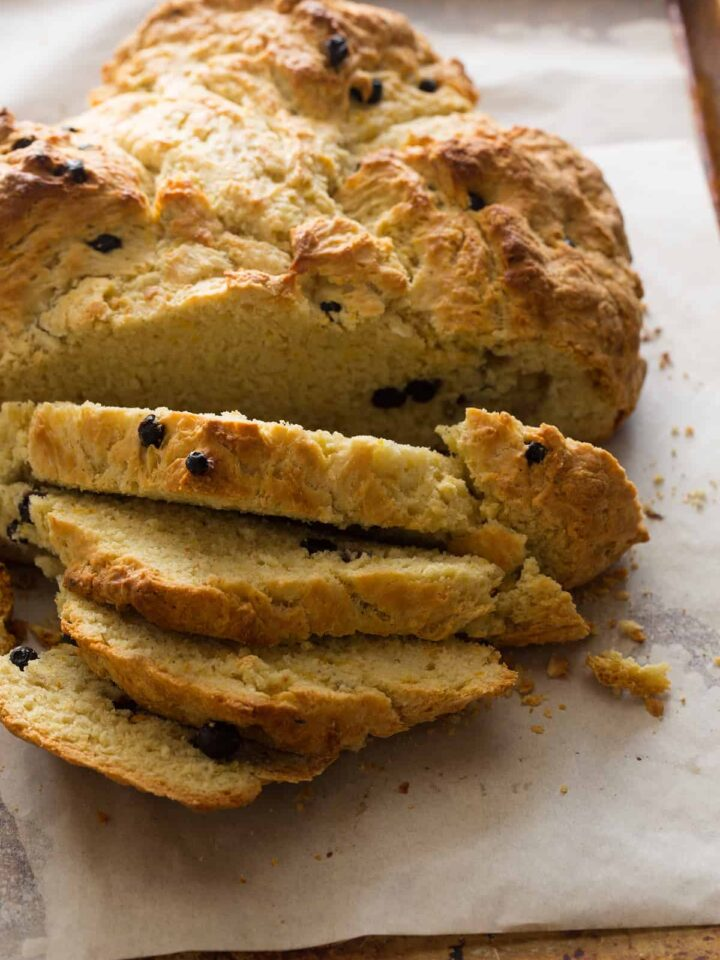 A close up of a sliced loaf of Irish soda bread with dried blueberries.