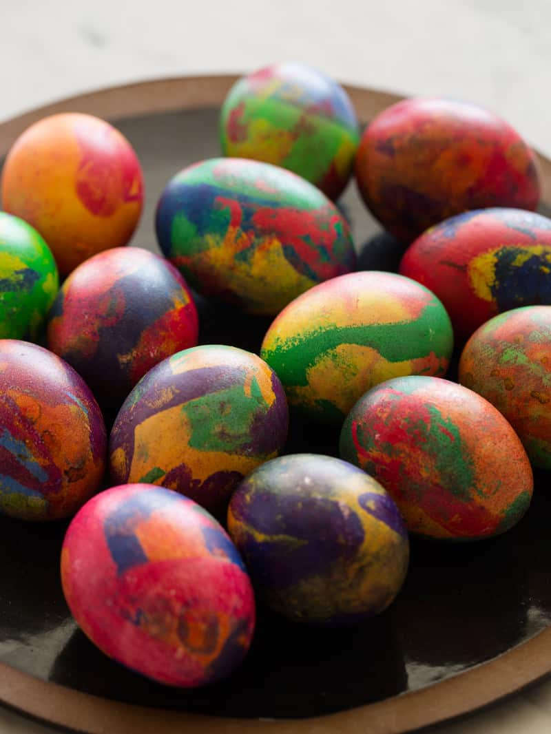 A plate of colorful painterly dyed Easter eggs.