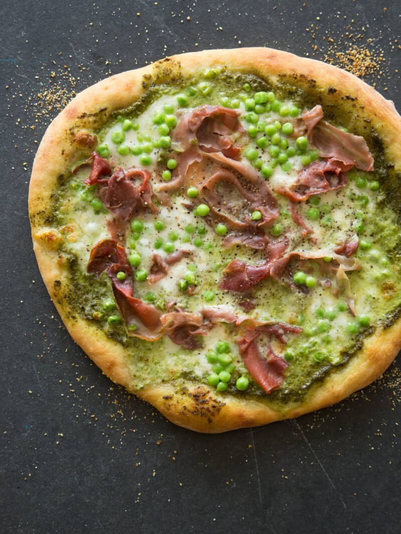 A whole English pea, prosciutto, and burrata pizza on a dark surface.