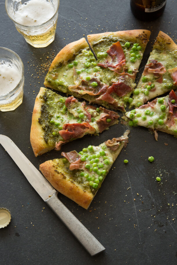 An english pea and proscuitto pizza cut into wedges with beer on the side.