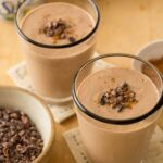 A close up of chocolate peanut butter and cinnamon smoothies in glasses with garnish.