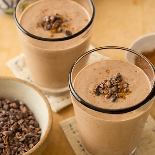 Chocolate peanut butter and cinnamon smoothies on a wood surface.