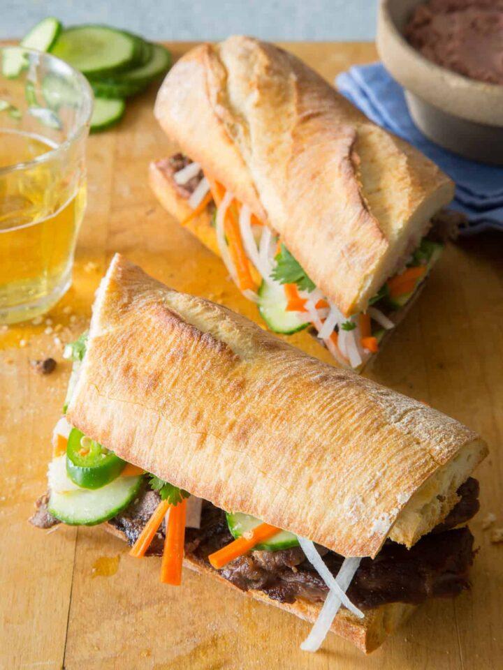Lemongrass beef Bahn Mi sandwiches on a wooden cutting board.