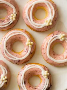 Close up of baked cherry doughnuts with cherry and vanilla glaze and white chocolate crispy balls.