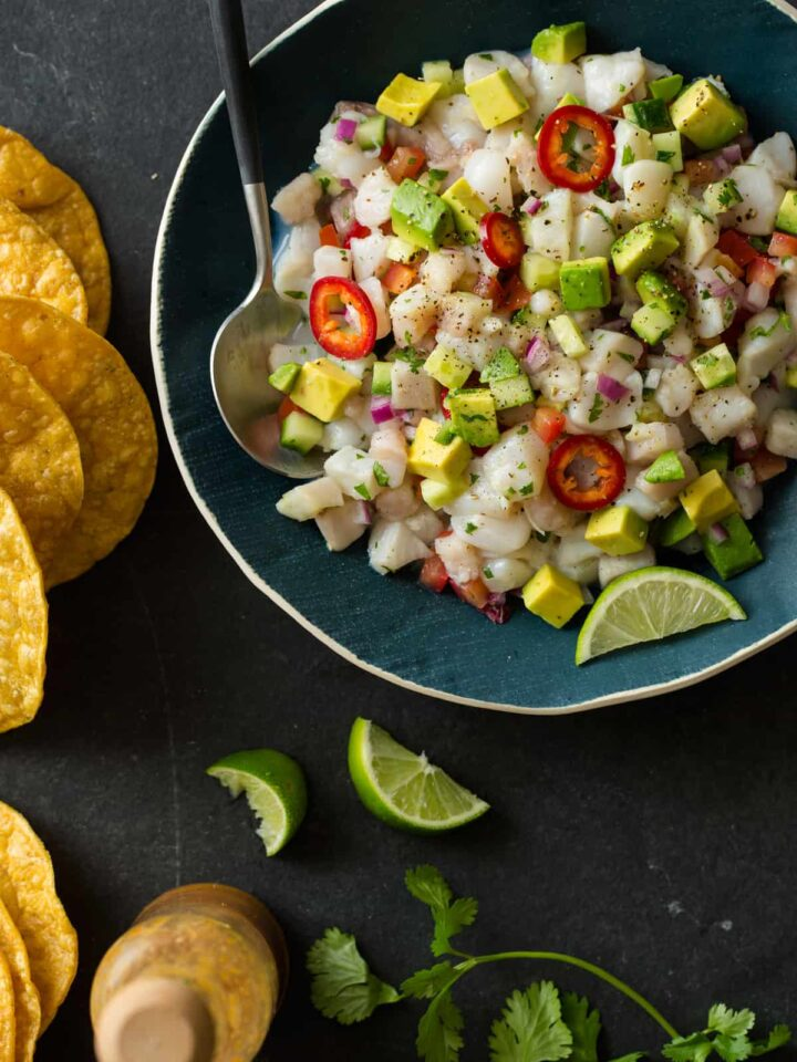 A bowl of simple ceviche with a spoon, chips and lime wedges.
