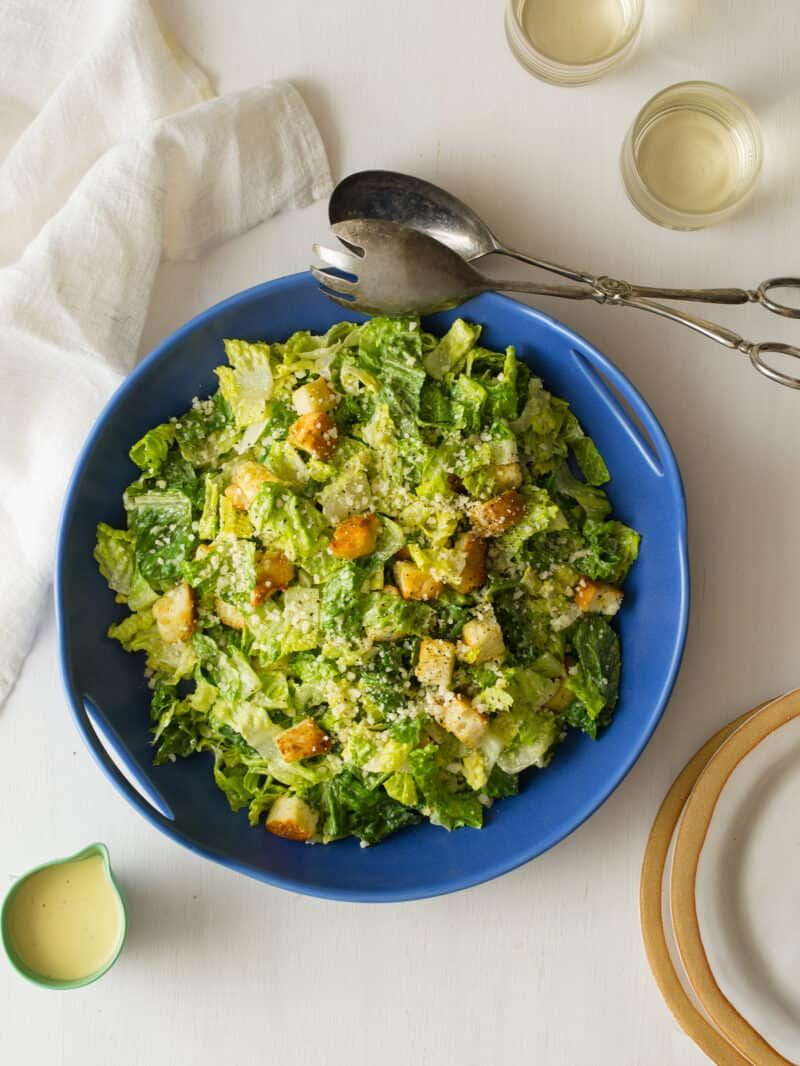 Classic Caesar salad in a blue bowl with salad tongs, extra plates, and dressing.
