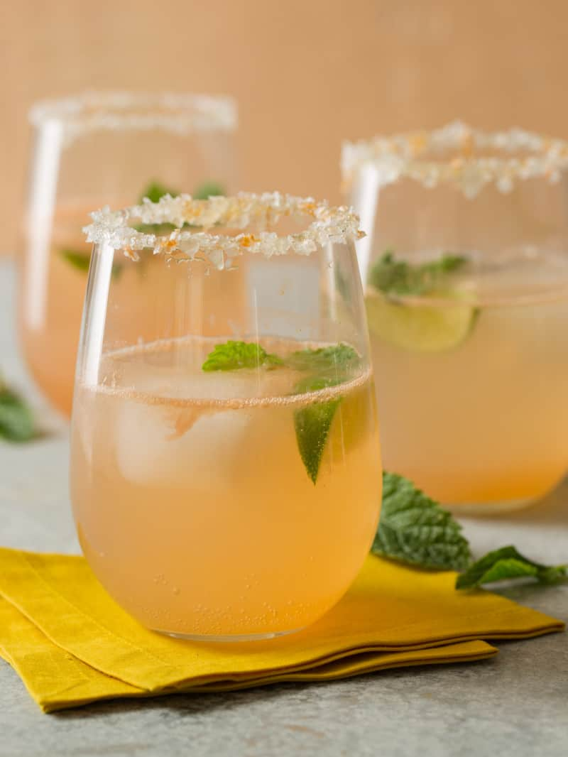 A close up of glasses of paloma with honey salt rim and fresh mint leaves.