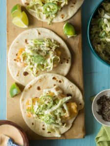Two Baja style fish tacos being made on a wooden cutting board.