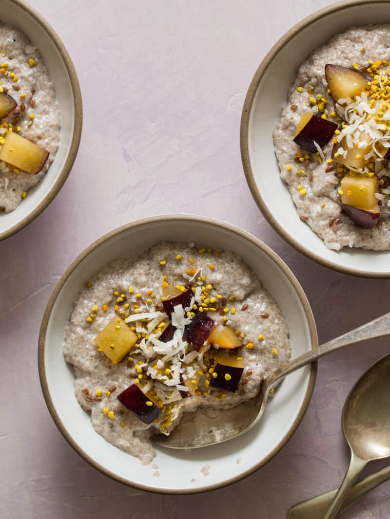 Bowls of chia seed pudding topped with fruit and shredded coconut with a spoon.