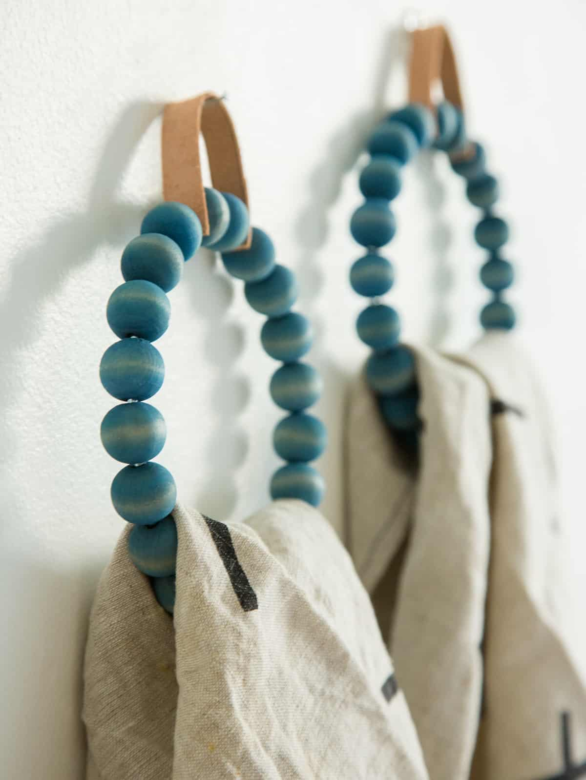 A close up of DIY beaded towel ring with towels hanging on them.