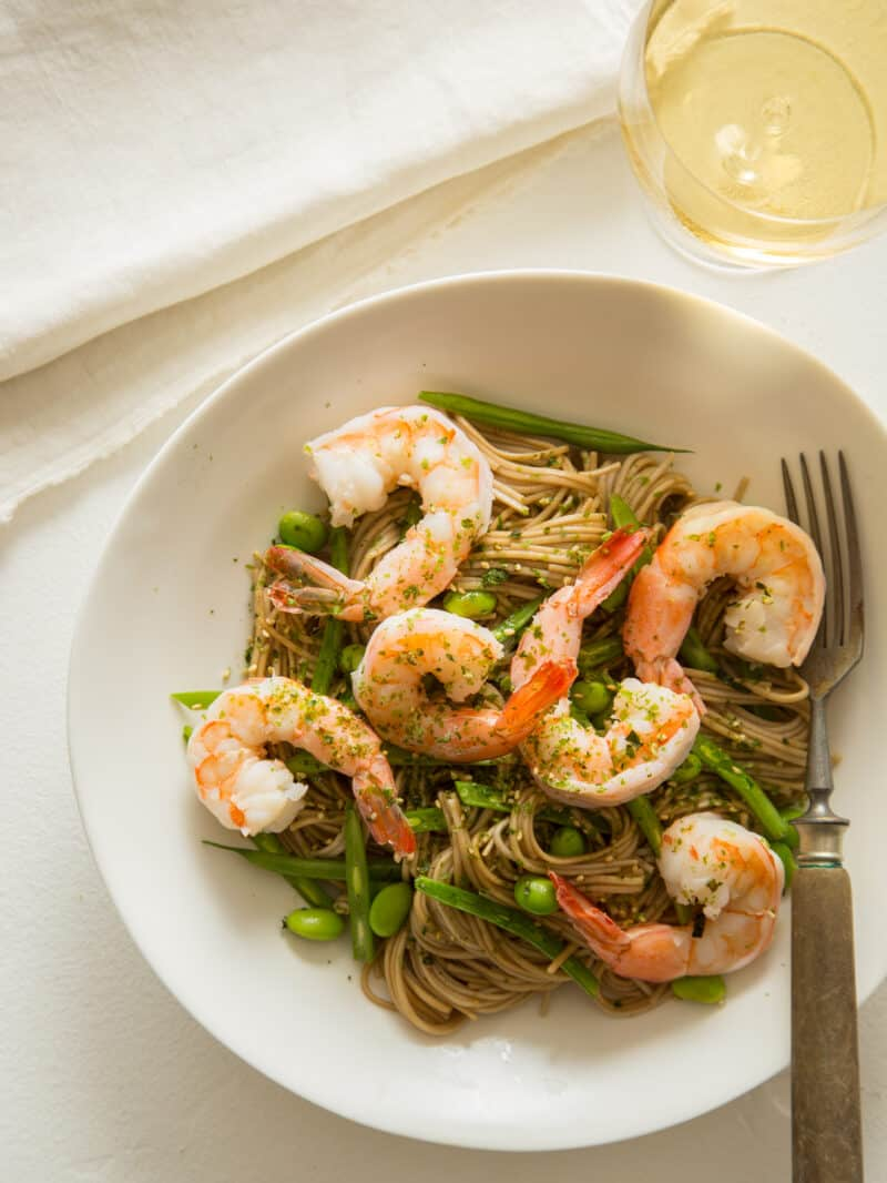 Sesame Soba Noodles with shrimp and a glass of wine on the side.