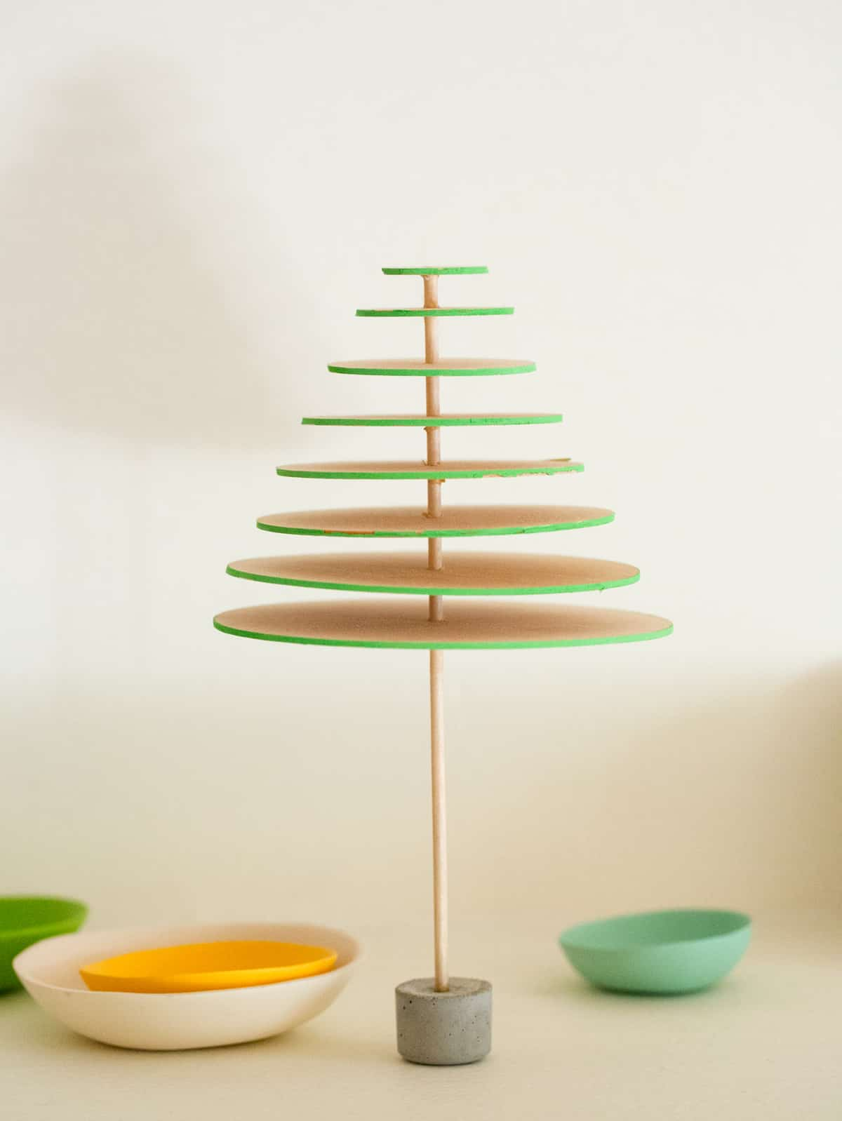 A DIY modern mini balsa wood Christmas tree with small bowls below.