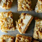 Individual streusel topped apple pie cheesecake bars.