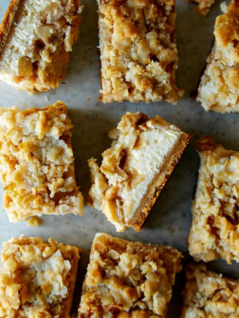 A close up of streusel topped apple pie cheesecake bars.